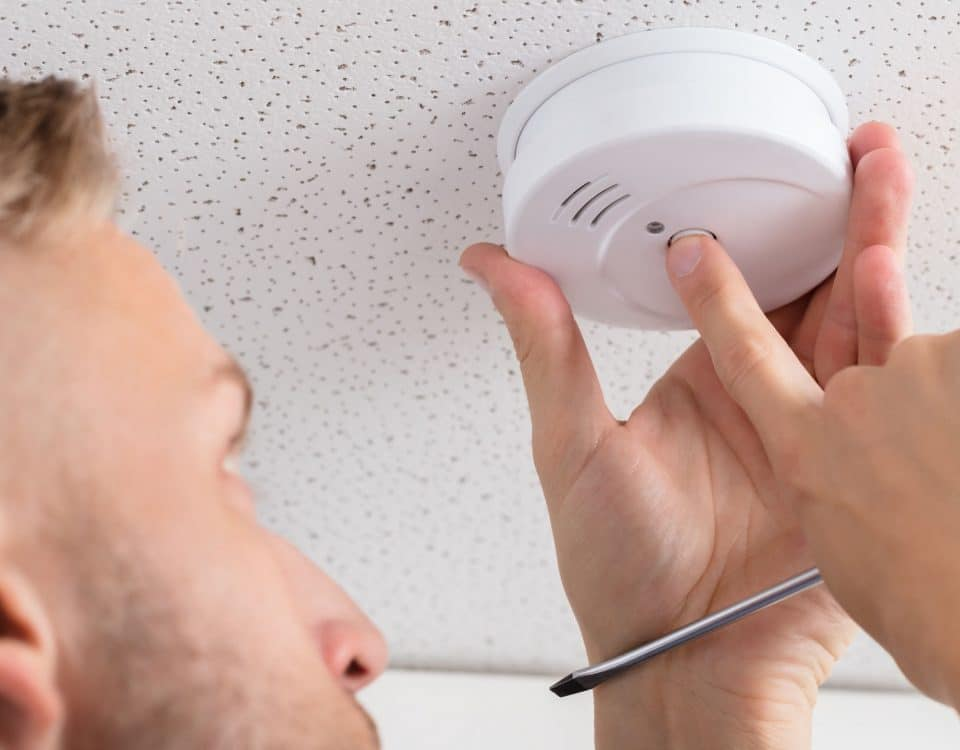 A Person's Hand Installing Smoke Detector On Ceiling Wall At Home
