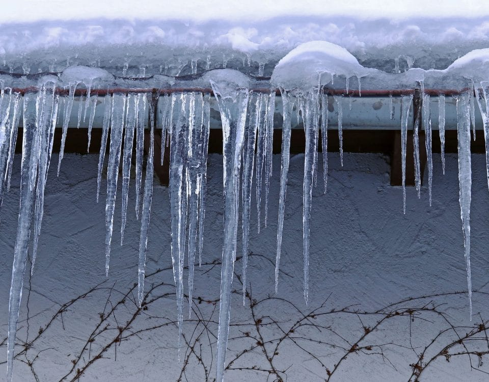 Large dangerous icicles on a house roof in winter