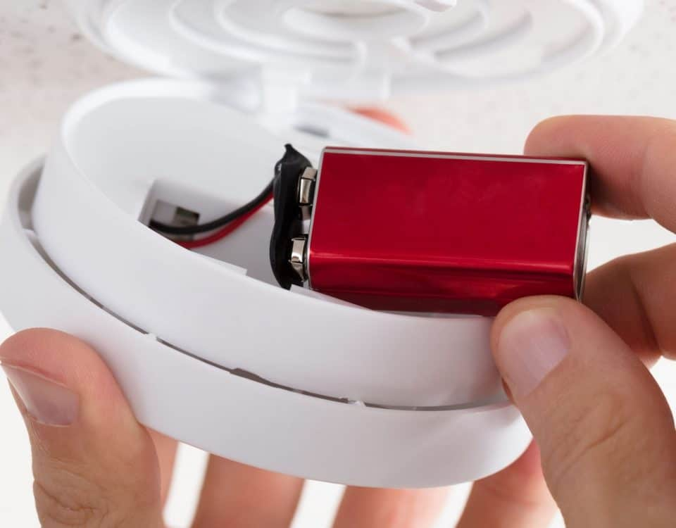 Close-up Of A Person's Hand Inserting Battery In Smoke Detector