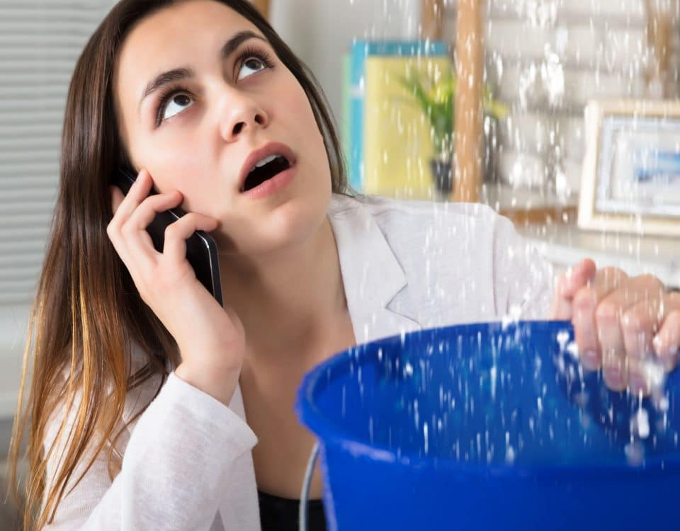 Woman holding bucket under leaking ceiling