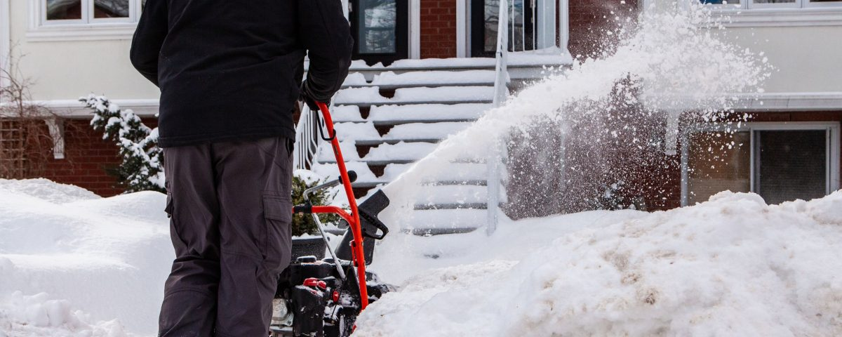 Man blowing snow and clearing the entrance of a house after a winter storm
