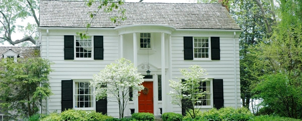 White formal house with siding, black shutters and bright green, manicured lawn and garden