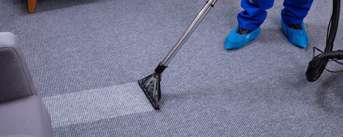 Man with carpet cleaner cleaning carpet