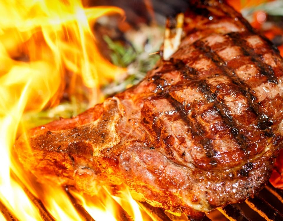 Steak and vegetables cooking on grill