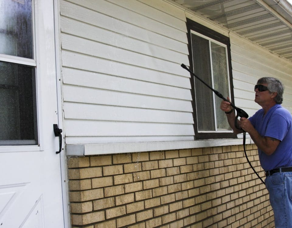 Home owner pressure washing the siding of his house